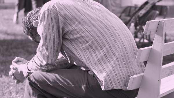 Man bent over praying