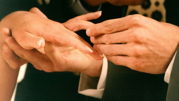 Close-up of ring being placed on bride